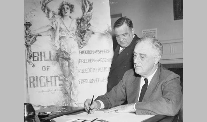 NYC Mayor Fiorello La Guardia watches President Roosevelt, sign a Bill of Rights Day proclamation at the White House, 1941
