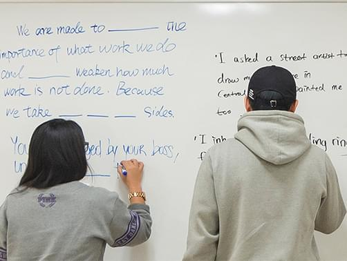 Students writing on the whiteboard