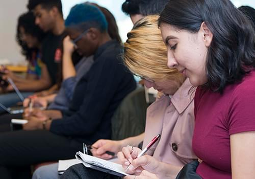 Students taking notes in an event
