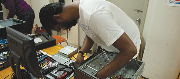 Student testing computer components in a class room